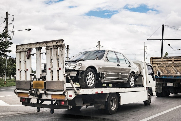 Uszkodzony samochód na lawecie po wypadku drogowym, w służbie drogowej