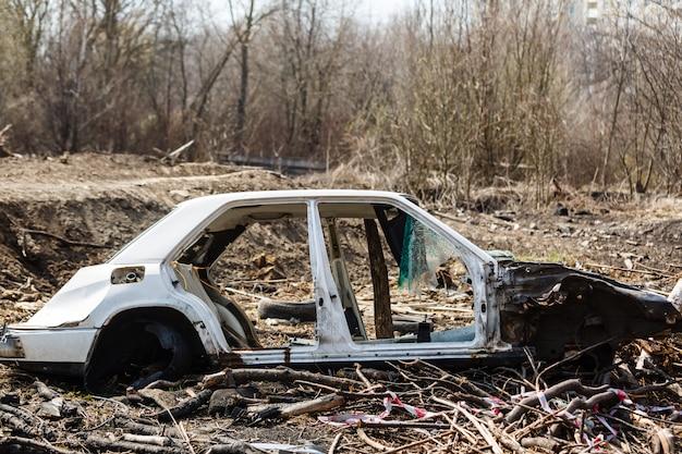 Uszkodzony samochód na wysypisku w polu