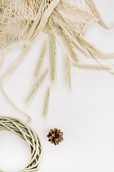 Uszy żytnie w woreczku ze sznurka, ramka na wieniec i stożek na białej powierzchni