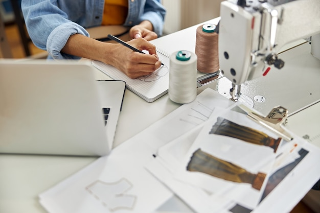 Utalentowana afroamerykanka krawcowa rysuje model ubrania w szkicowniku siedząc w miejscu pracy