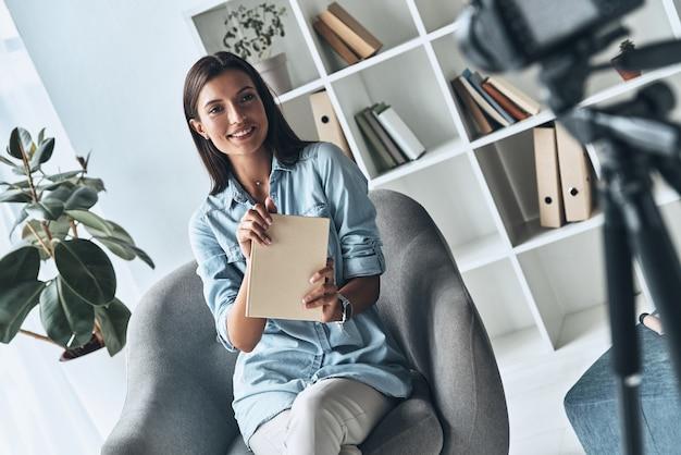 Utalentowana kobieta. atrakcyjna młoda kobieta wskazująca miejsce na kopię i uśmiechnięta