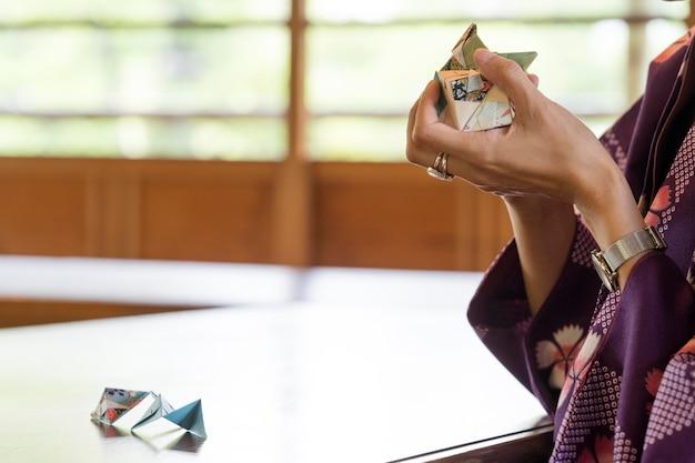 Utalentowana kobieta robi origami z japońskim papierem