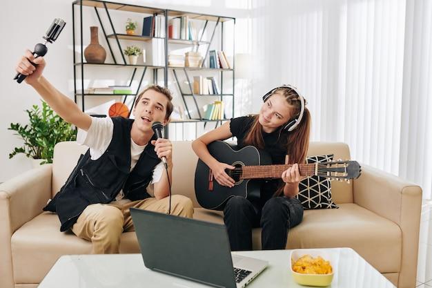 Utalentowana, kreatywna para nastolatków, która nagrywa się, śpiewając i grając na gitarze