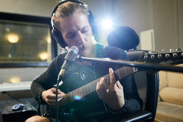 Utalentowany gitarzysta hipster nagrywa nową ścieżkę dźwiękową