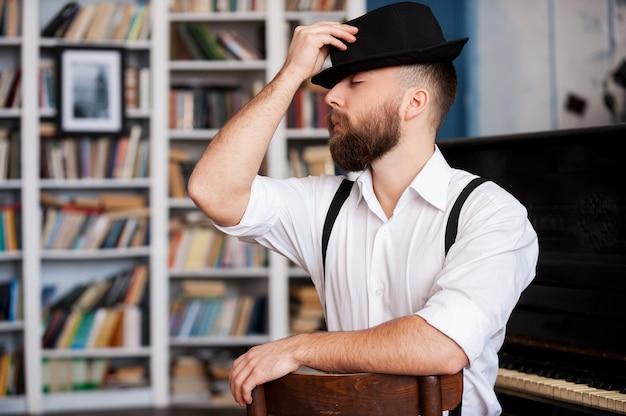 Utalentowany i kreatywny. portret przystojnych młodych brodatych mężczyzn siedzących przed fortepianem z zamkniętymi oczami