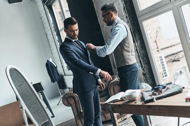Utalentowany krawiec. młody modny projektant pomagający swojemu klientowi się ubrać