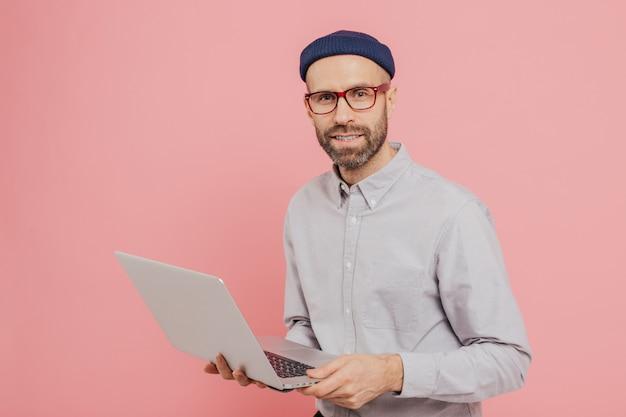 Utalentowany męski dziennikarz o atrakcyjnym wyglądzie, trzyma nowoczesny laptop