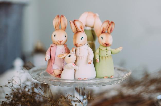 Сute rodzina zabawkowych królików na szklanej tacy wśród wystroju i roślin. wielkanocne rodzinne wakacje koncepcja.