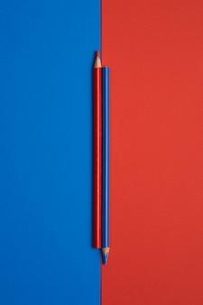 Utknąłem czerwone i niebieskie kolorowe kredki na niebieskim i czerwonym stole