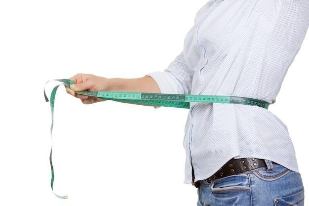 Utrata masy ciała i koncepcja zdrowego stylu życia. fitness kobieta mierząca talię za pomocą taśmy mierniczej ekstremalne zbliżenie
