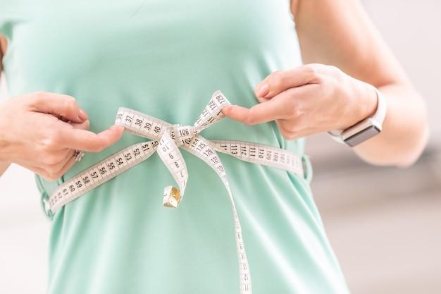 Utrata masy ciała i szczupłe ciało młodej kobiety. dziewczyna pomiaru jej talii ciała taśmą mierniczą.