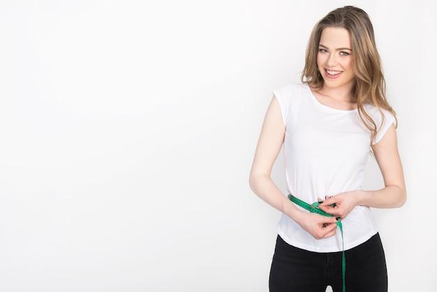 Utrata masy ciała, śledzenie wyników i postępów, dieta i koncepcja zdrowia. młoda dziewczyna trzyma miarkę wokół talii.
