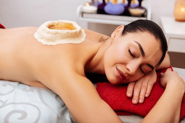 Utrzymanie na miejscu. ciemnowłosa spokojna kobieta spokojnie leżąca na łóżku masującym i ciesząca się wszystkimi dobrodziejstwami zabiegu