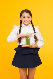 Utrzymuję energię. szczęśliwy energiczny uczeń trzymając butelkę soku na żółtym tle. mała dziewczynka z warkoczami z długimi włosami czuje się zdrowa z napojem energetycznym. inteligentny i energiczny.