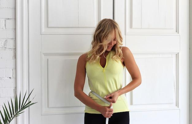Utrzymywać formę. młoda kobieta o atletycznym ciele mierzy talię typem miary