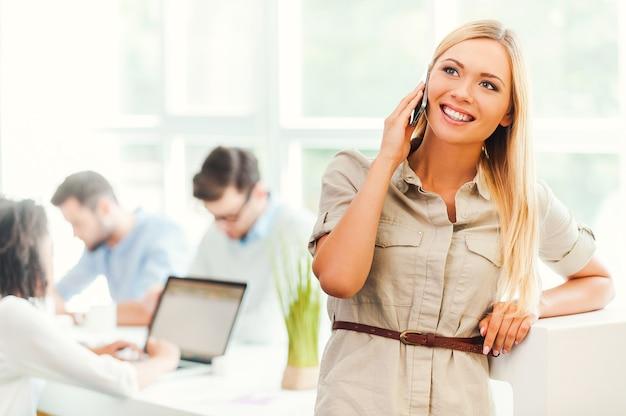 Utrzymywanie kontaktu z klientami. wesoła młoda kobieta rozmawia przez telefon komórkowy i uśmiecha się, podczas gdy jej koledzy pracują w tle