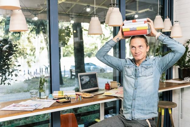 Utrzymywanie równowagi. przyjemny młody człowiek zakładający książki na głowę, znudzony nauką