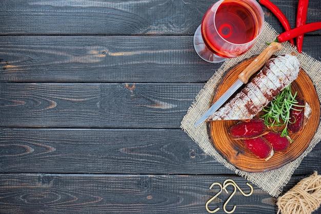 Utwardzona bresaola w plasterkach z przyprawami i kieliszkiem czerwonego wina na ciemnym drewnianym tle rustykalnym.