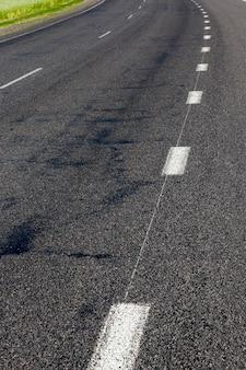Utwardzona droga do ruchu różnych pojazdów, stara droga z ubytkami na asfalcie