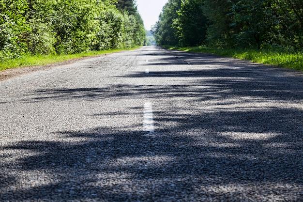 Utwardzona droga publiczna z białymi znakami drogowymi dla pojazdów, słoneczny dzień