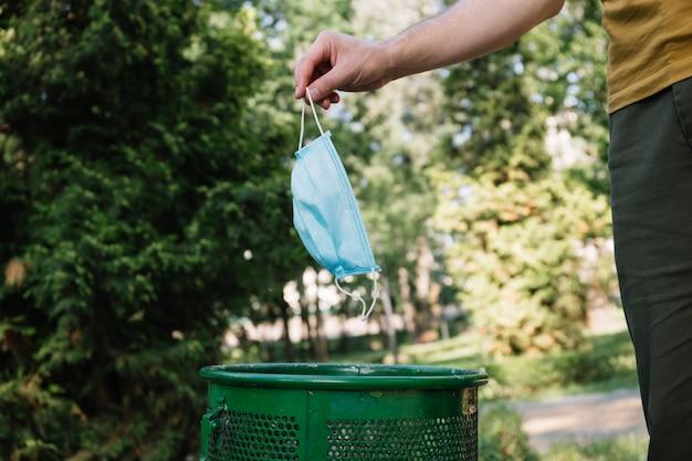 Utylizacja starej maski medycznej. ręka wrzucająca używaną maskę ochronną do kosza na śmieci w parku