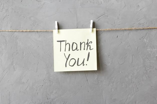 Uwaga dziękuję jest napisana na żółtej naklejce, która wisi wraz ze spinaczami do bielizny na szarym tle
