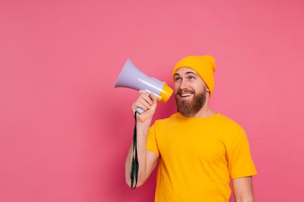 Uwaga! europejski mężczyzna krzyczy w megafon na różowym tle