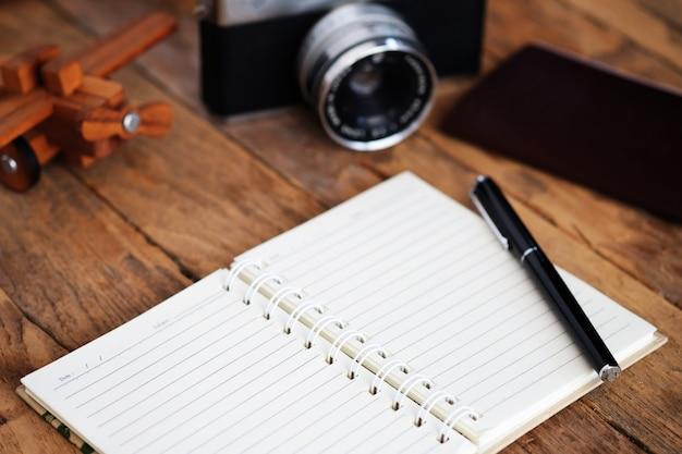 Uwaga książka i podróże wakacje elementy na drewnianym stole.