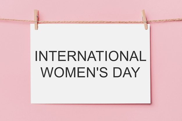 Uwaga list pin na linie na różowym tle, miłość i koncepcja valentine z tekstem międzynarodowy dzień kobiet