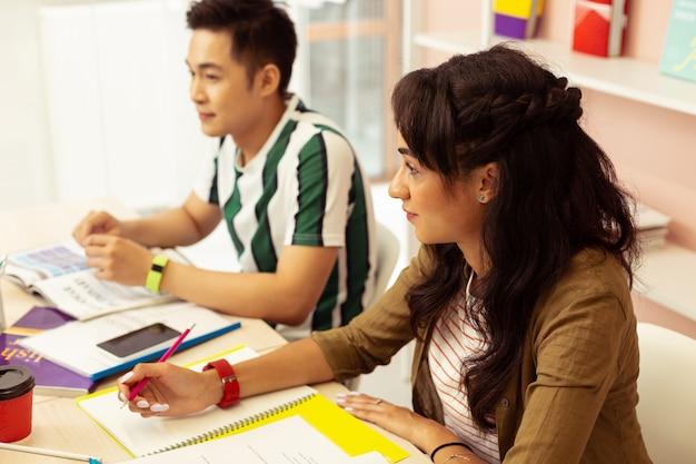 Uwaga na lekcji. dość długowłosa dziewczyna z uśmiechem na twarzy patrząca na swojego nauczyciela