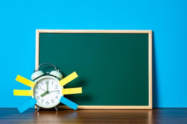Uwaga papier lepki i vintage budzik i pusta zielona tablica