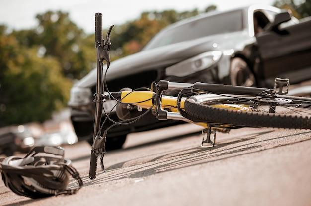 Uwaga, uważaj. upadły rower i kask leżący na drodze przed czarnym samochodem osobowym w letni dzień