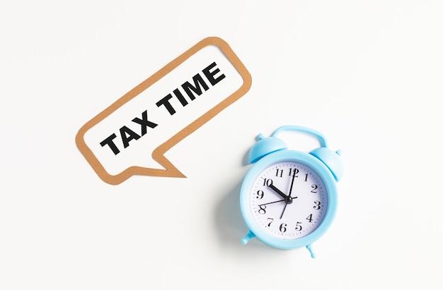 Uwaga wiadomość czasu podatku na białej tablicy z czerwonym zegarem retro