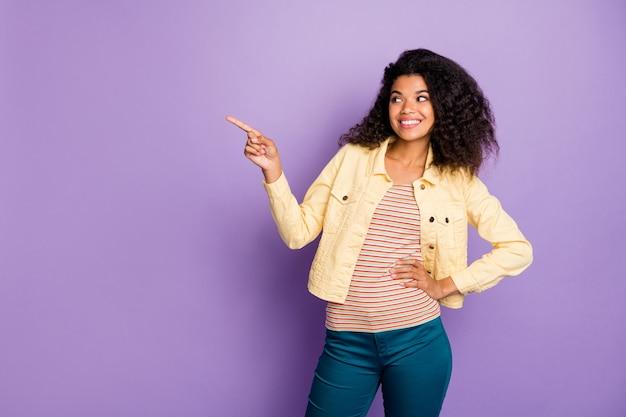 Uwaga wiadomości ze zniżką pozytywna dziewczyna afroamerykańska wskazująca palec wskazujący copyspace poleca reklamy sugerują promocyjne noszenie nowoczesnej odzieży niebieskie spodnie spodnie izolowane fioletowe tło