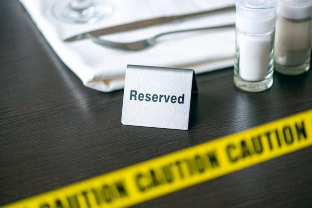 Uwaga - żółta taśma na stole w kawiarni lub restauracji i znak zastrzeżony. dystans społeczny