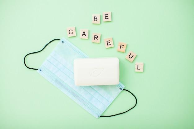 Uważaj i mydło i ochronna maska medyczna na jasnozielonym tle