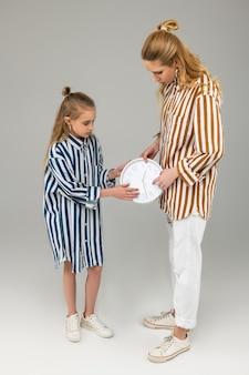 Uważna długowłosa kobieta w pomarańczowej koszuli w paski, wskazująca na czas na zegarze, nosząc go z młodszą siostrą