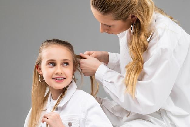 Uważna dorosła pani w białej koszuli zbiera włosy swojej młodszej siostry w cienkie warkocze podczas wspólnego spędzania czasu