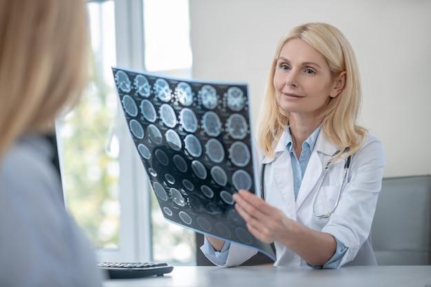Uważna, inteligentna lekarka ze skanem mrt i pacjentem omawiającym wyniki badania