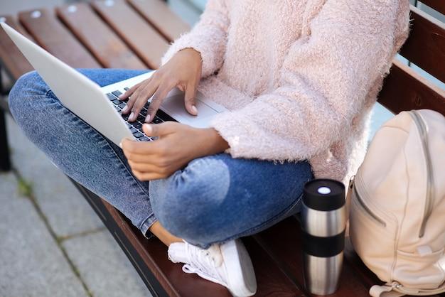 Uważna inteligentna, produktywna dziewczyna łapiąca moment ładnej pogody i siedząca w parku podczas pracy na swoim laptopie nad swoim zadaniem uniwersyteckim