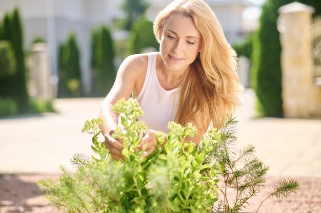 Uważna kobieta dbająca o kwiaty w pobliżu domu