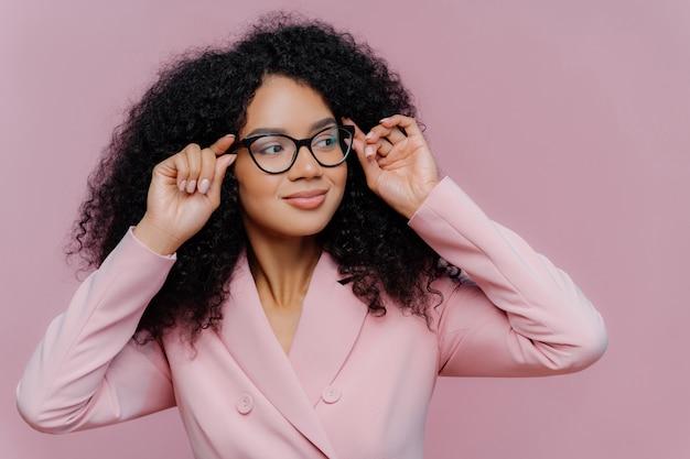 Uważna kobieta trzyma ręce na ramce okularów, patrzy na niego z dystansem, nosi różowy garnitur