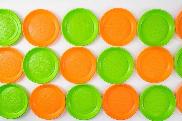 Uważna konsumpcja. kolorowe, jasnozielone i pomarańczowe jednorazowe talerze leżące w rzędach jako instalacja artystyczna