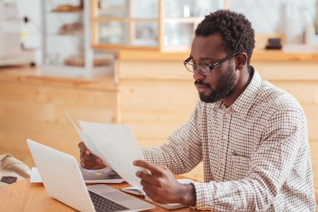 Uważna lektura. przystojny młody mężczyzna w okularach siedzi w kawiarni i czyta dokumenty w jego rękach