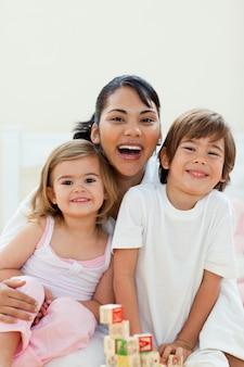 Uważna matka i jej dzieci bawiące się zabawkami z kostek