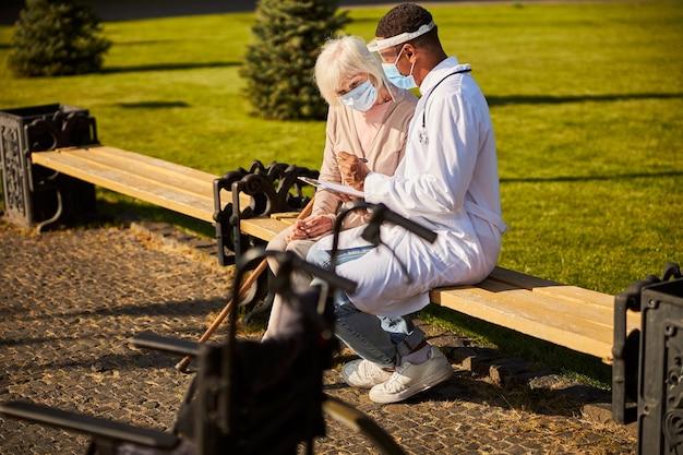 Uważna starsza kobieta uważnie analizująca informacje w zeszycie lekarza, siedząc razem na podwórku