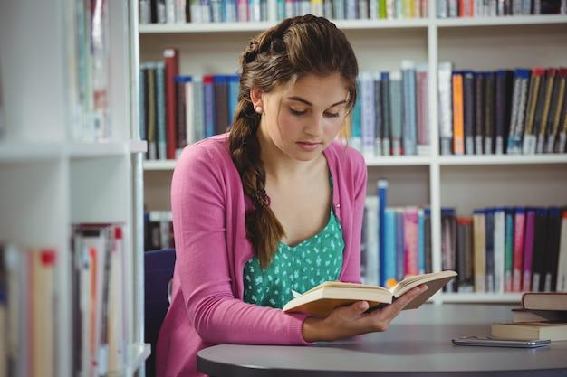 Uważna uczennica czytanie książki w bibliotece