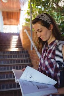 Uważna uczennica do czytania książki w pobliżu schodów