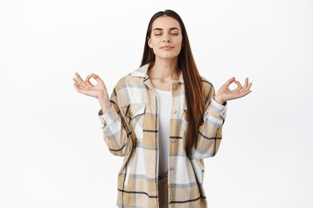 Uważna uśmiechnięta kobieta medytuje, oddycha zrelaksowany z zamkniętymi oczami i pozie nirwany zen, ćwiczy jogę, odpoczywa, czuje spokój i ulgę, stoi nad białą ścianą pacjenta