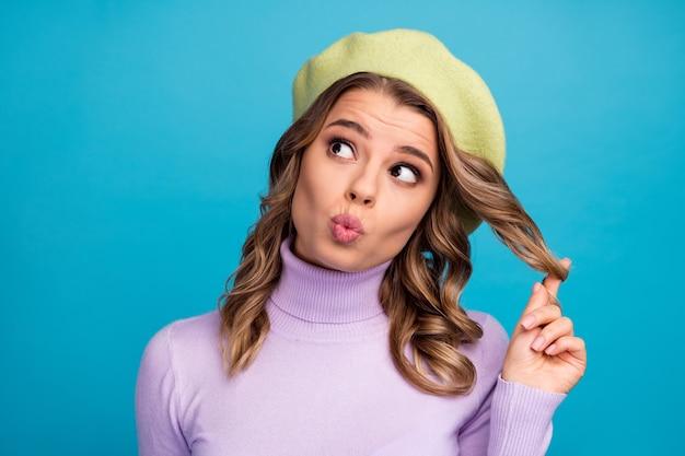 Uważna zainteresowana dziewczyna dotyka fryzury, myśli, że myśli decydują o wysłaniu pocałunku na niebieską ścianę